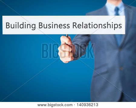 Building Business Relationships - Businessman Hand Holding Sign
