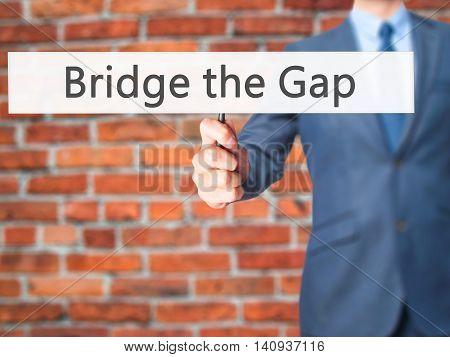 Bridge The Gap - Businessman Hand Holding Sign