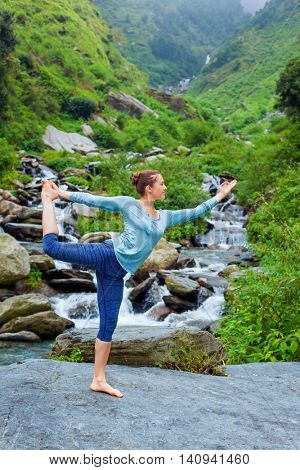 Yoga outdoors - woman doing yoga asana Natarajasana - Lord of the dance balance pose outdoors at waterfall in Himalayas