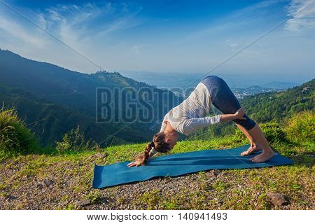 Yoga outdoors - young sporty fit woman doing Ashtanga Vinyasa Yoga asana Adho mukha svanasana - downward facing dog variation - outdoors in Himalayas in the morning