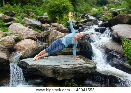 Yoga outdoors - beautiful sporty fit woman doing yoga asana Vasisthasana - side plank pose at tropical waterfall