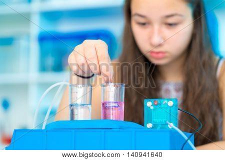 Girl schoolgirl experimenting hydrogen fuel cell