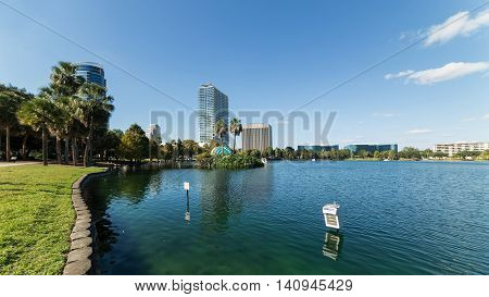 Orlando Lake Eola in the morning with urban skyscrapers and clear blue sky. Florida