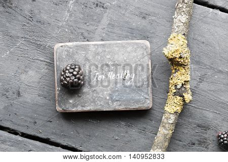 Eat heathy inscription and blackberries on a wooden table.