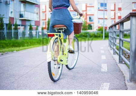 Back View Of Young Woman In Dress Riding Vintage Bike With Basket