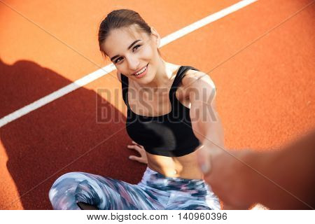 Smiling attractive young woman athlete getting up and taking somebody hand on stadium