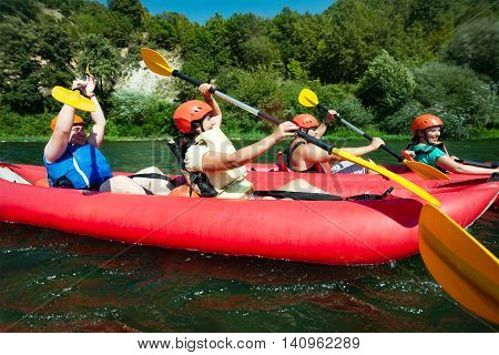 Two teams in red inflatable canoes having fun  with the vesals in calm waters of a river.