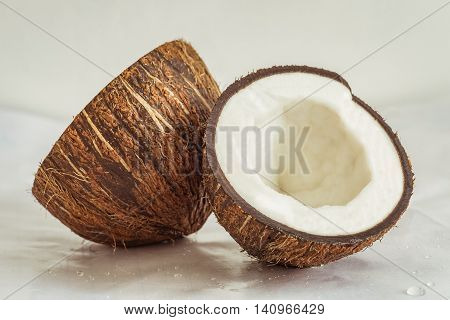 Two fresh halves of coconut on a soft glossy surface