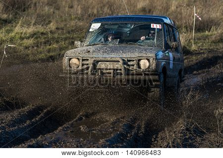 LvivUkraine- December 6 2015: Unknown rider on the off-road vehicle brand Land Rover overcomes a route off road near the city of Lviv Ukraine