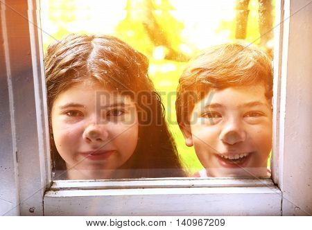 teen siblings couple brother and sister close up photo through the window on the summer garden background