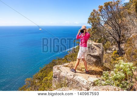Nature travel photographer woman taking pictures on a spectacular cliff during the trekking Fluted Cape Within the South Bruny National Park Bruny Island, Tasmania Australia. poster