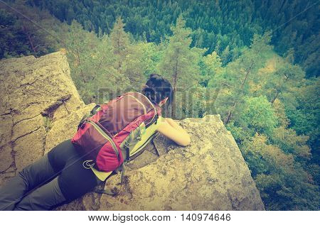 SLOVAK PARADISE, SLOVAKIA - AUGUST 17, 2015: A tourist on the precipice with mountains in the background in vintage style. Young woman on the precipice in Slovak Paradise National Park.