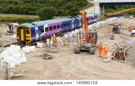 ILKESTON ENGLAND - AUGUST 1: A train passes by construction workers on site next to a section of railway track. In Ilkeston Derbyshire England. On 1st August 2016.