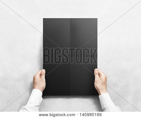 Hand holding black folded blank poster mockup, isolated. Arm in shirt holds clear broadsheet template mock up. Broadside pure print display show. Sticking a3 poster on the wall.