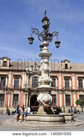 SEVILLE, SPAIN - September 13, 2015: Tourists by the marvellous water fountain and lamp at the Plaza Virgen de los Reyes on September 13, 2015 in Seville, Spain