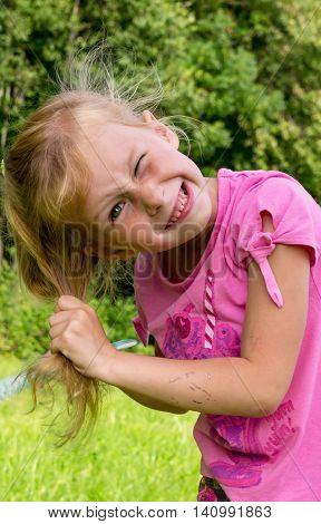 little blond girl in a pink jacket combs hair on nature, green bushes in the background, angry, her hair mussed, grimassy, girl, portrait