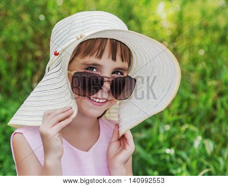 Little girl wearing a hat, looking coquettishly from under the big sunglasses on the background of green grass.