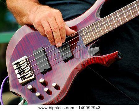 Male musician playing an electric bass guitar.