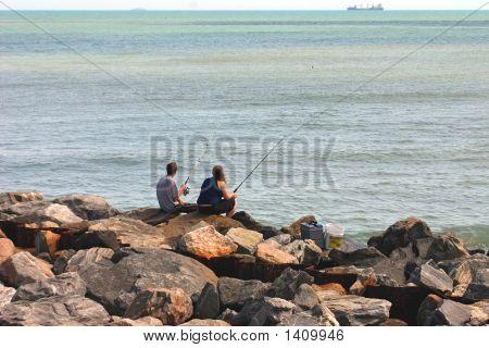 Couple Fishing On Rocks