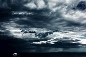 Alone white little boat on sea and dark storm clouds poster