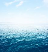 Blue sea with waves and clear blue sky poster