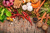 Assortment of Thai food Cooking ingredients .Red curry paste ingredients of thai popular food on rustic wooden background. Spices ingredients chili pepper garlicgalangal and Kaffir lime leaves . poster
