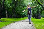 Woman walking on path in green summer park poster