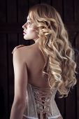 Sexy and sensual young woman in lingerie, corset with long curls posing poster