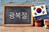 a chalkboard with the text National Liberation Day of Korea written in Korean and a flag of South Korea, on a rustic wooden surface, against a blue wooden background poster
