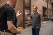 Kapap instructor demonstrates self defense techniques against a gun poster