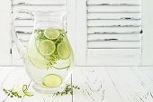 Cucumber infused hydrating water with thyme and lime. Homemade flavored lemonade on rustic old wooden table poster