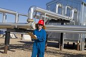 female gas field operator in full safety gear completes daily duties poster