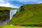 Grand waterfall Skogafoss. Near a waterfall put some colorful tourist tents.  poster