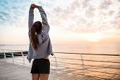 Young beautiful brunette sportive girl training at sunrise over seaside. Copy space. poster
