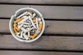 Various cigarette butts in dirty full ashtray poster