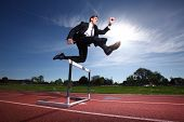 Businessman jumping over hurdle poster