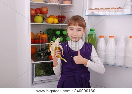 Girl Is Holding A Banana On The Refrigerator Background. Beautiful  Girl Near The Fridge With Health