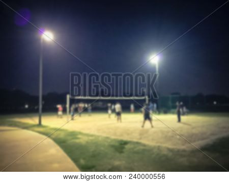 Abstract Blurred People Playing Volleyball On Open Air Sand Court At Evening