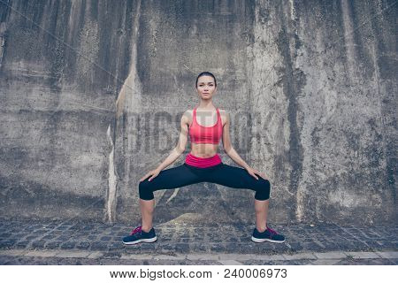 Young Fashionable Sportswoman Is Stretching On The Street On A Summer Day. She Is Very Bendy And Fle