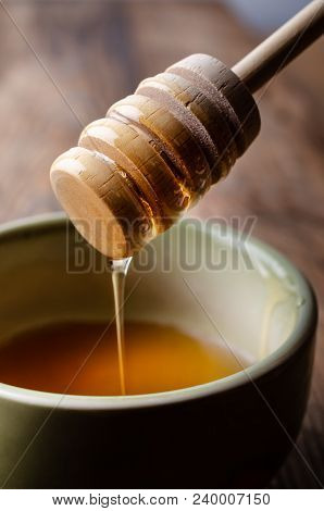 A Coated Wooden Drizzler, Lifting And Dripping Clear, Golden Honey Over A Green Ceramic, Partly Fill