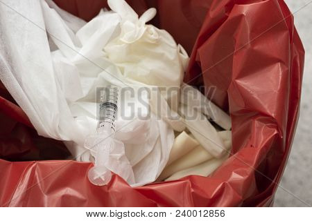 Used surgical gloves, gauzes and syringe in a red garbage bin for biohazard disposal poster