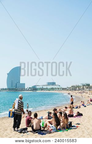 BARCELONA, SPAIN - APRIL 27, 2018: Sunbathers at the Barceloneta Beach in Barcelona, Spain, with the W Hotel, also known as Hotel Vela or Sail Hotel, in the background