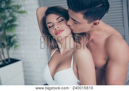 Close Up Of Beautiful Half Naked Couple Is Embracing In The Bed Room, Man Kissing His Lover In Cheek