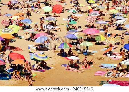 SITGES, SPAIN - JULY 9, 2017: People enjoying, relaxing or sunbathing at the Garraf Beach in Sitges, a popular beach in the coast of the Metropolitan Area of Barcelona, in Catalonia