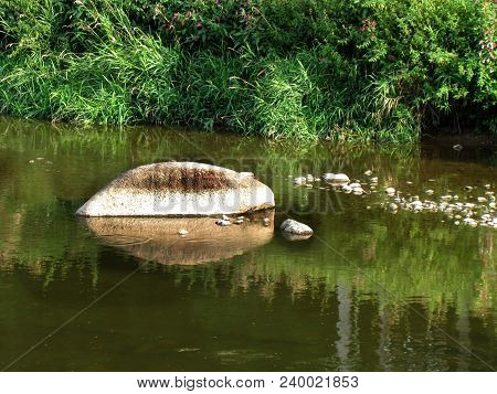 Stones In The River, A Rock Protruding Above The Water Surface, An Idyllic Natural Shot