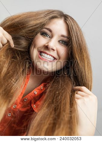 Happy Positive Woman With Long Brown Hair Presenting Her Healthy Hairdo. Haircare Concept.