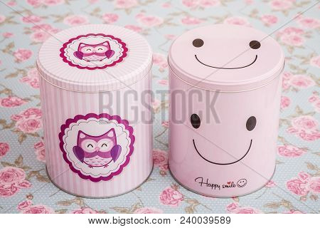 Colorful Pink Tin Storage Containers On Floral Pattern