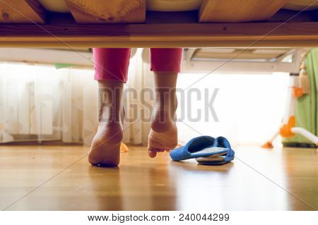 Toned Image From Under The Bed On Young Girl In Pajamas Searching For Slippers
