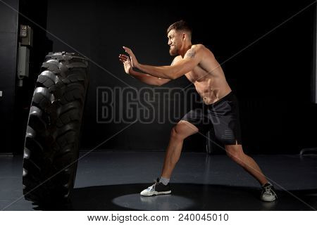 Crossfit training. Muscular young man flipping tire at gym