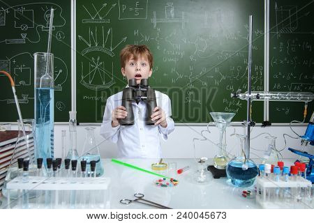 Schoolboy looks through binoculars by a chalkboard on a chemistry lesson. Educational concept.